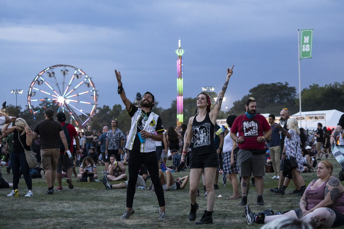 Festival-goers dance in Douglass Park as storm clouds roll in on Day 2 of Riot Fest on Friday evening.