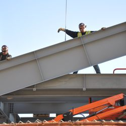 Steel being lowered into position in the left-field bleachers -