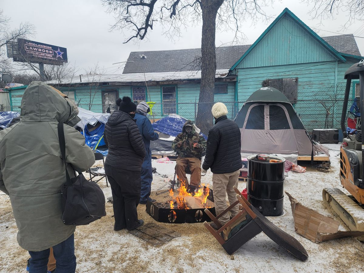 Individuals stand around an outdoor fire in coats. Snow is on the ground, and there's a green house in the background.