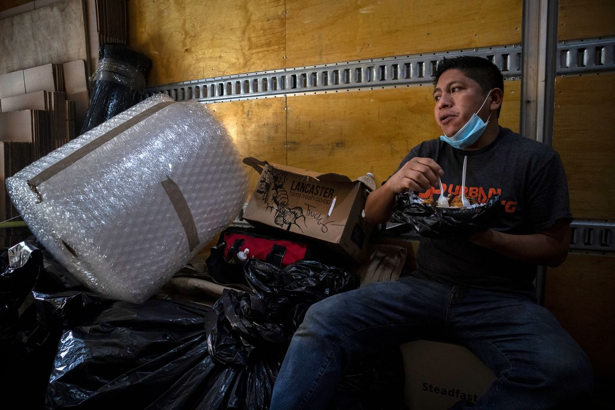 After loading the truck, Felix Ortega eats a plate of chicken and white rice in the back of the truck six while sitting on a box of tape on Friday, Aug.14, 2020.