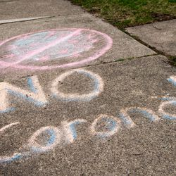 """""""No Corona!"""" written in chalk on the sidewalk outside a home in the 400 block of Addison Road in Riverside, Monday, April 6, 2020."""