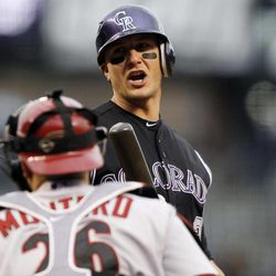 Colorado Rockies' Troy Tulowitzki, top, reacts to a called strike three as Arizona Diamondbacks catcher Miguel Montero heads back to the dugout to end the first inning of a baseball game in Denver, Saturday, April 14, 2012.