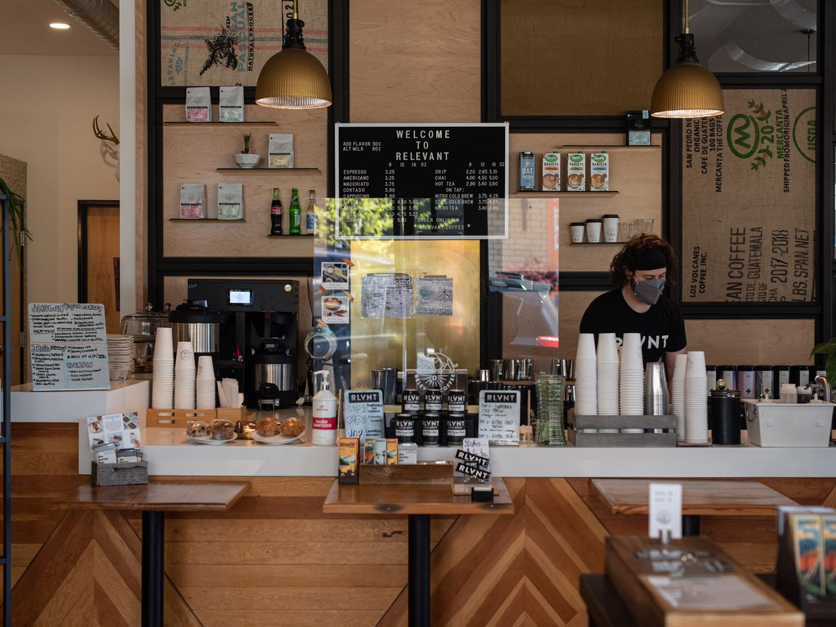 A barista with a face mask works behind the counter at Relevant Coffee in Vancouver, Washington, surrounded by pantry items, paper cups, and coffee-making equipment.