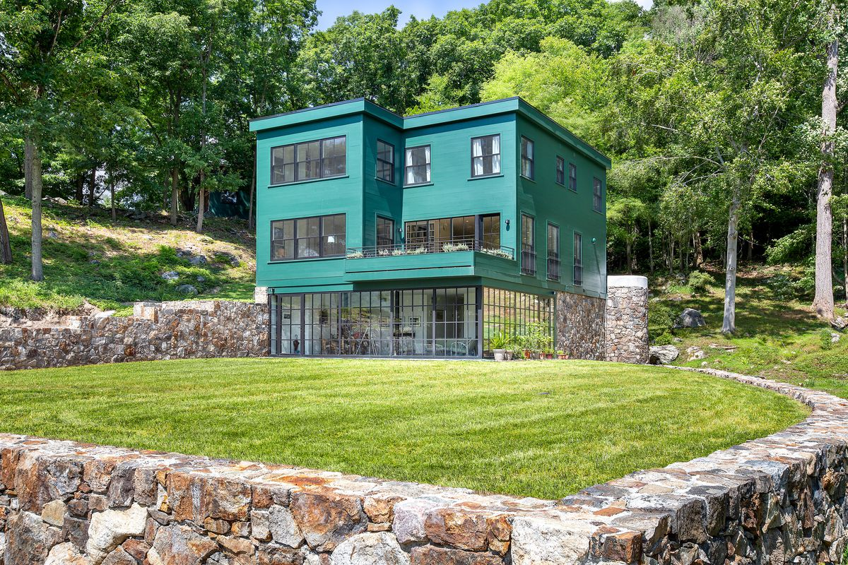 An exterior view of a boxy green house set on green grass with trees behind it.