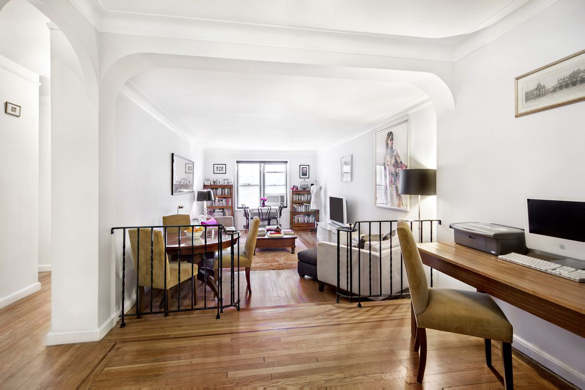 A living area with hardwood floors, a desk with a computer, white walls, and arched entryways.