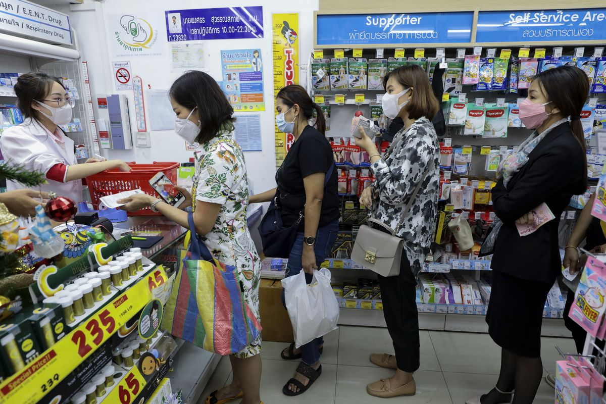 People wearing breathing masks wait in line at a pharmacy to buy face masks in Thailand.