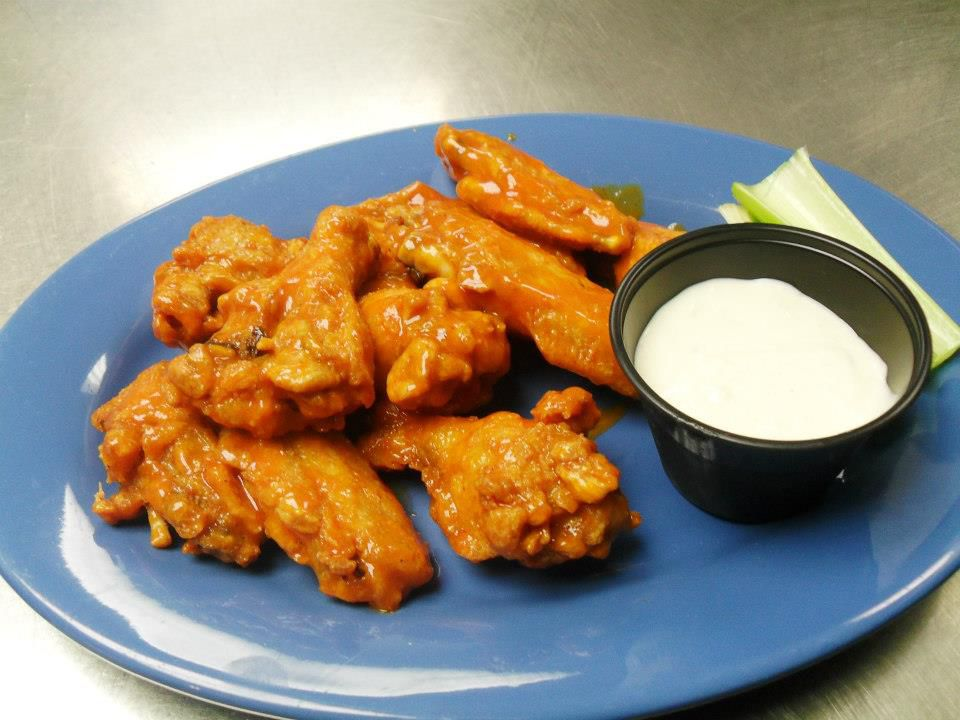Several buffalo wings with dipping sauce and a lone stick of celery on a blue plate