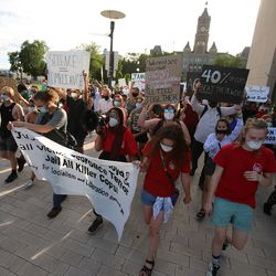 A large group of demonstrators march from Washington Square Park to the Salt Lake City Public Safety Building in Salt Lake City on Monday, June 1, 2020, while chanting for justice.