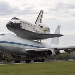 The space shuttle Discovery, sitting atop a 747 carrier aircraft, lands at Dulles International Airport in Chantilly, Va., Tuesday, April 17, 2012. Discovery, the longest-serving orbiter will be placed to its new home, the Smithsonian's National Air and Space Museum's Steven F. Udvar-Hazy Center in Chantilly, Va.