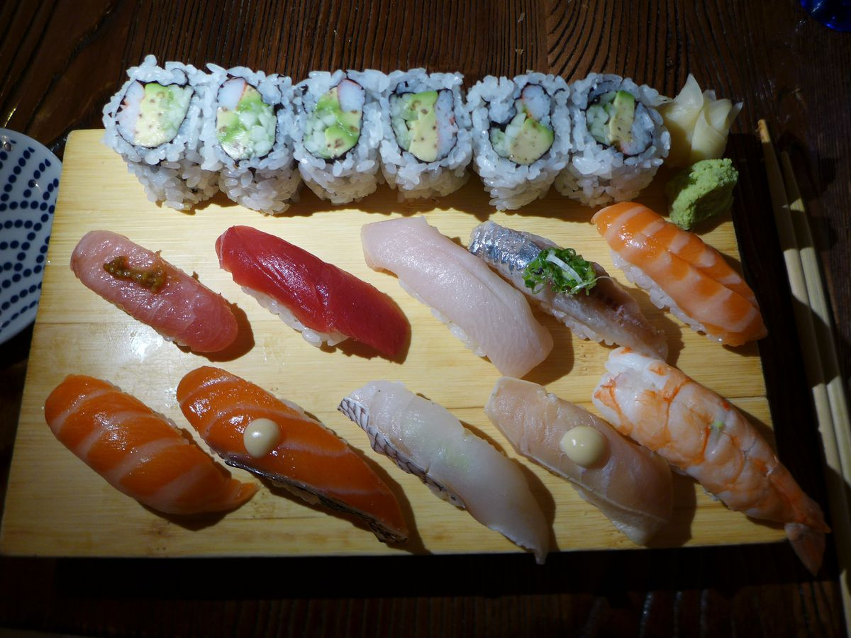 An array of sushi including finger sushi and a sushi roll served on a wooden block.