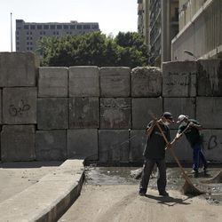 Egyptian street cleaners clean up the area around the U.S. embassy in Cairo, Egypt, Saturday, Sept. 15, 2012 after days of protests near the U.S. embassy over a film insulting Prophet Muhammad.