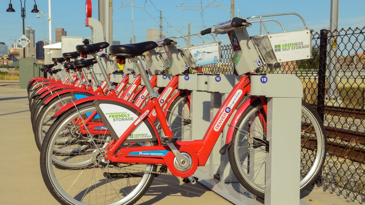 A row of bright red B-Cycle bikes parked at a bike-share station next to train tracks with a city skyline in the distance.