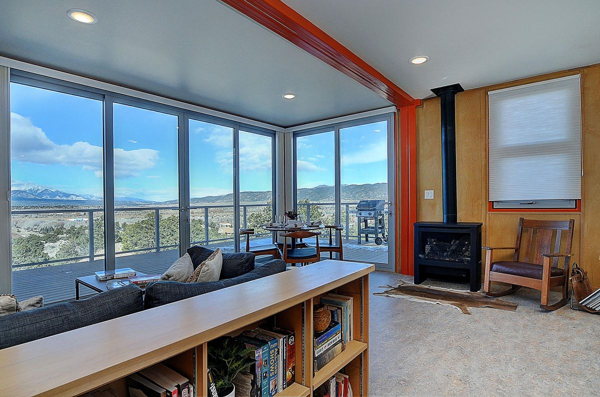 A living room has large glass windows that overlook a deck, a stove, and bookshelves.