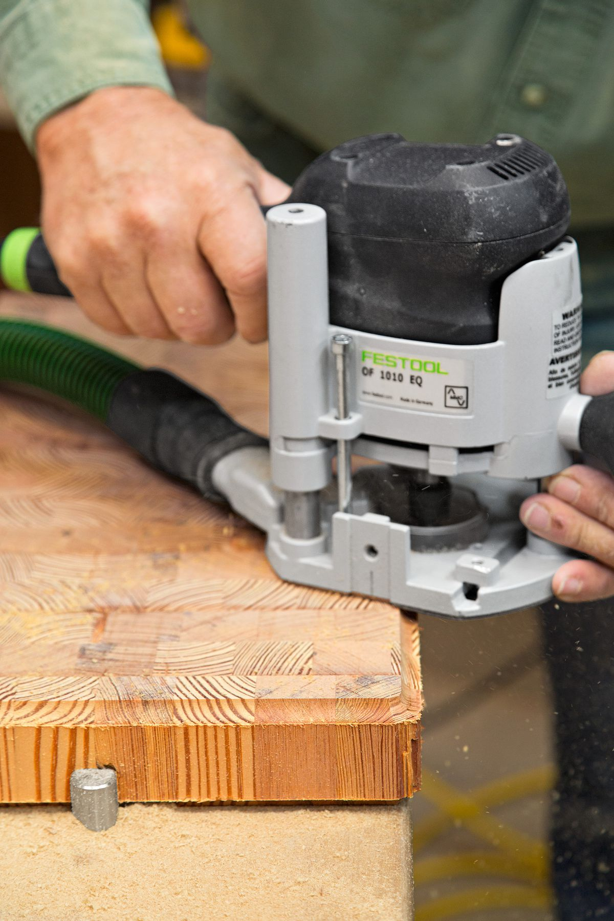 Person using router on wood to finish end grain cutting board.