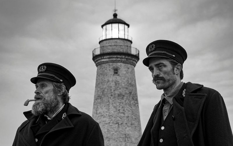 Thomas (Willem Dafoe) and Ephraim (Robert Pattinson) in front of the lighthouse.