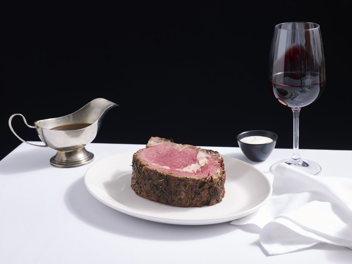 A plate of rare prime rib at Del Frisco's, with jus and red wine in the background