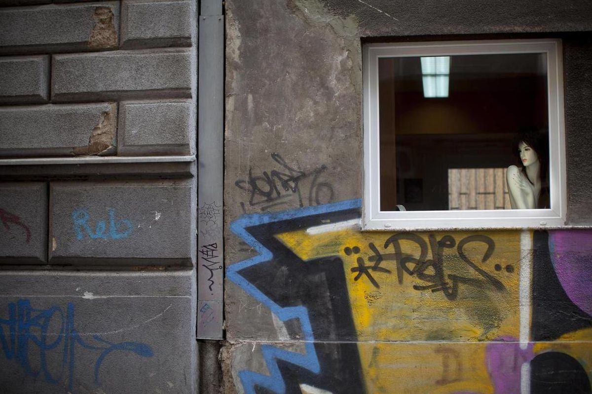 A mannequin is placed next to a window of a building marked with graffiti in the center of Sarajevo, Bosnia, Thursday, April 5, 2012. Sarajevo marks the 20th anniversary of the start of the 44-month Bosnian Serb siege of Sarajevo, part of the 1991-95 Bosn