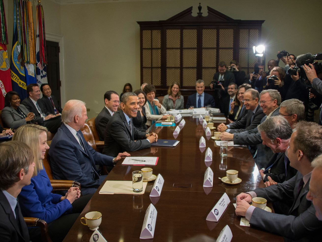 Tech executives meet with members of the Obama administration at a large conference table.