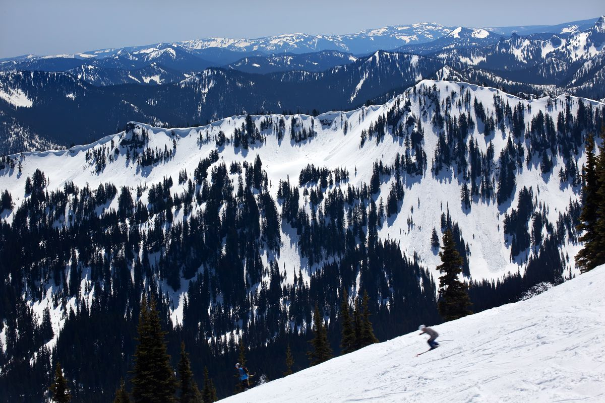 At the bottom right, a skier is slightly blurry from motion along a white slope. Behind the ridge the skier is on, there's a snow- and evergreen-covered mountain, with more mountains cascading behind it.