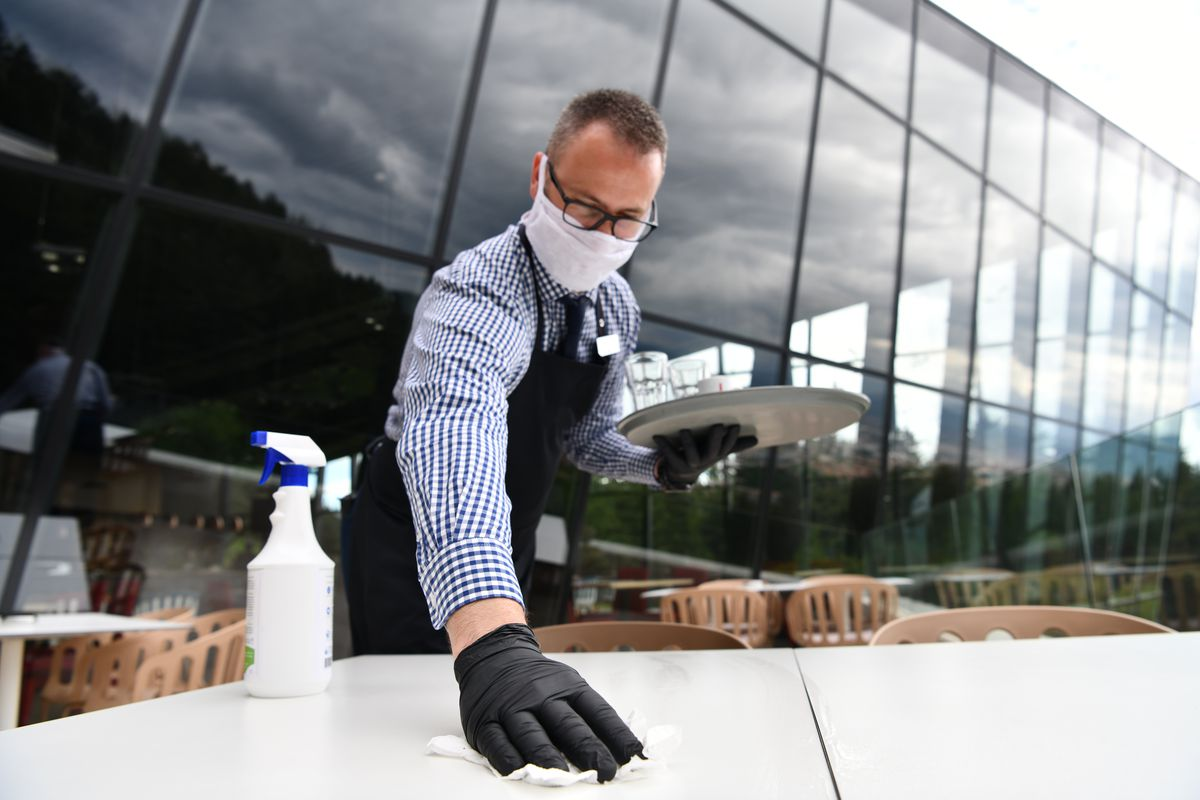 A man in a button-up shirt and glasses wipes down a table with gloves