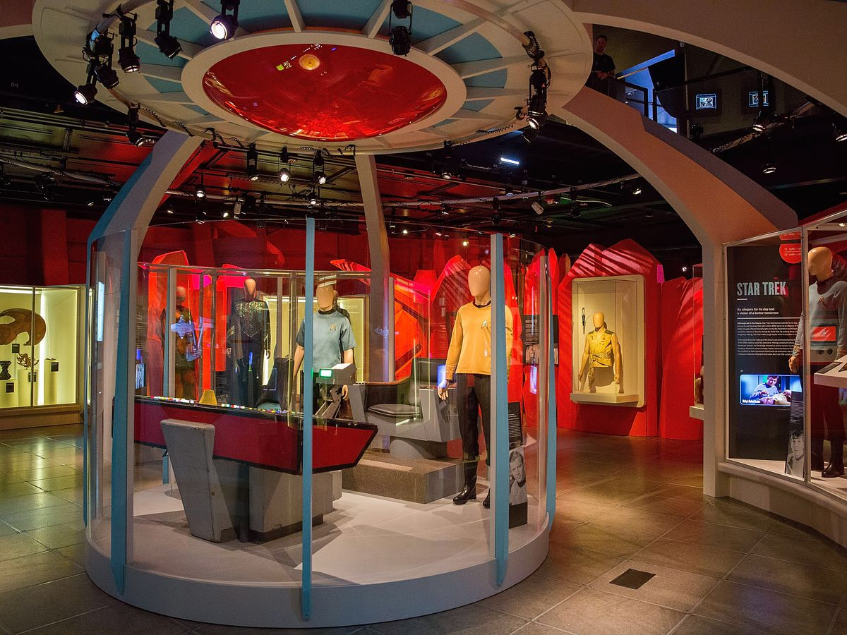 The interior of the Museum of Pop Culture.  There is a display area with statues of the characters from the original Star Trek television series. On the walls are various glass windows with other items from the series.