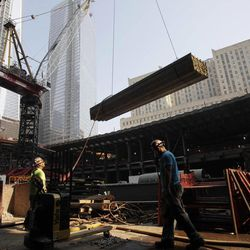 In this Friday, Sept. 7, 2012 photo, an ironworker watches as a crane lifts a load of construction supplies at the World Trade Center transportation hub, in New York. The new transportation hub at the trade center will connect 13 subway lines and PATH trains to New Jersey when it opens in 2015.