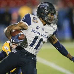 Utah State's Savon Scarver (11) carries the ball on a kick return during the first half of the Frisco Bowl NCAA college football game against Kent State on Friday, Dec. 20, 2019, in Frisco, Texas.