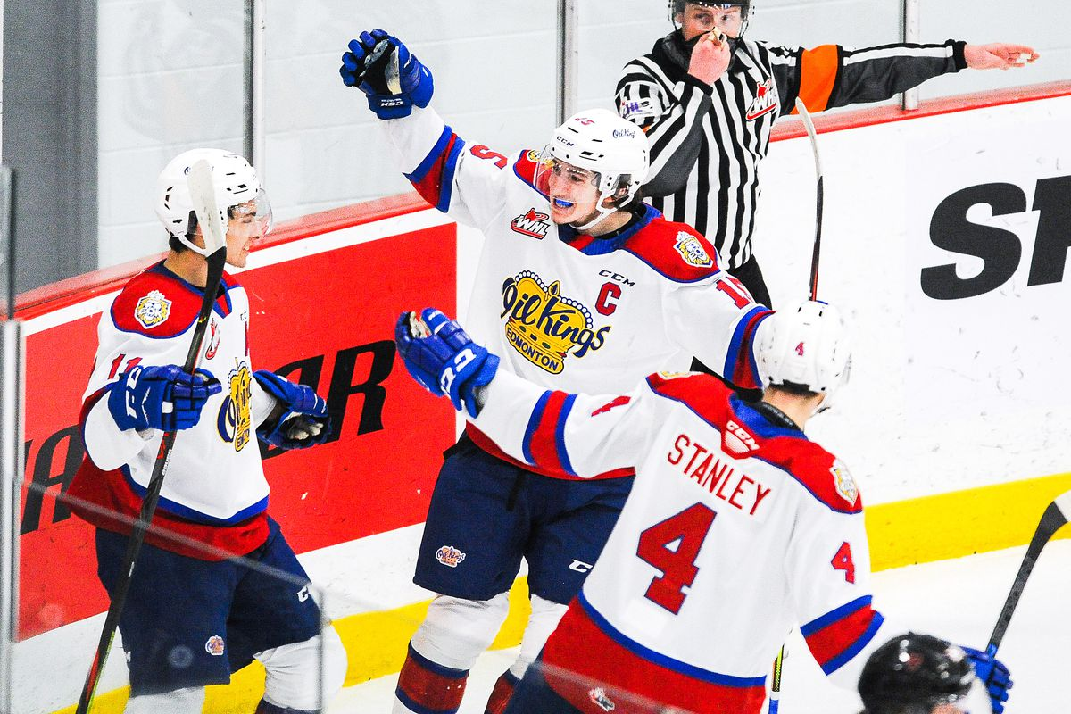 Dylan Guenther #11 (L) of the Edmonton Oil Kings celebrates with his teammates Scott Atkinson #15 (C) and Ross Stanley #4 (R) after scoring against the Calgary Hitmen during a WHL game at Seven Chiefs Sportsplex on March 27, 2021 in Calgary, Alberta, Canada.