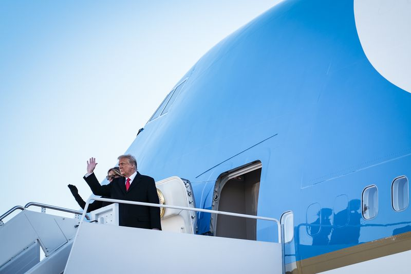 President Donald Trump and first lady Melania Trump wave to supporters as they board Air Force One to head to Florida on January 20, 2021.