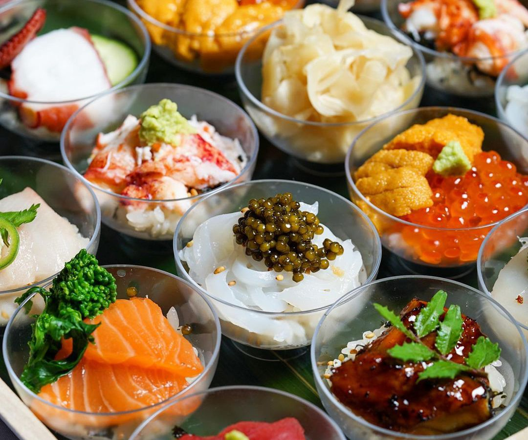 Raw fish and sashimi dishes in small glass containers