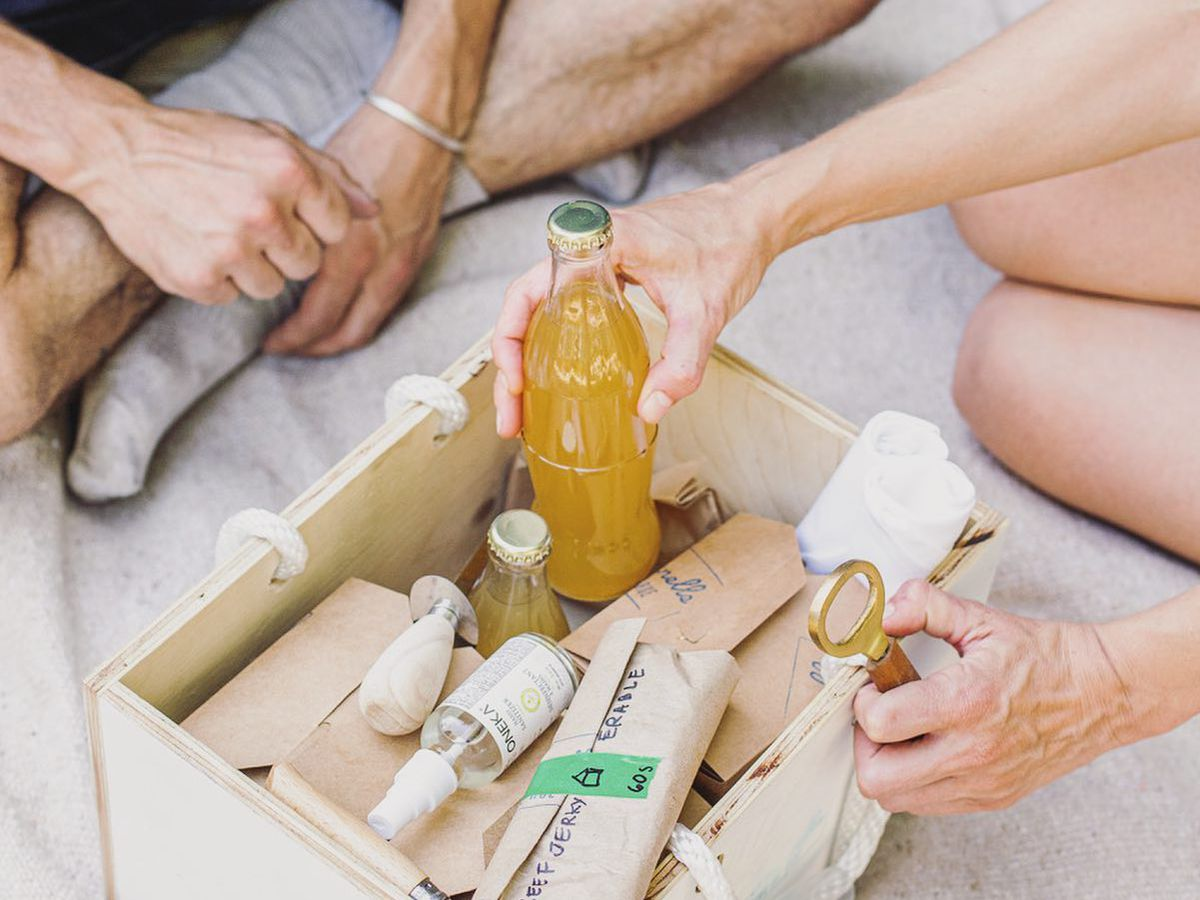 picnic kit with two people, one holding a bottle opener