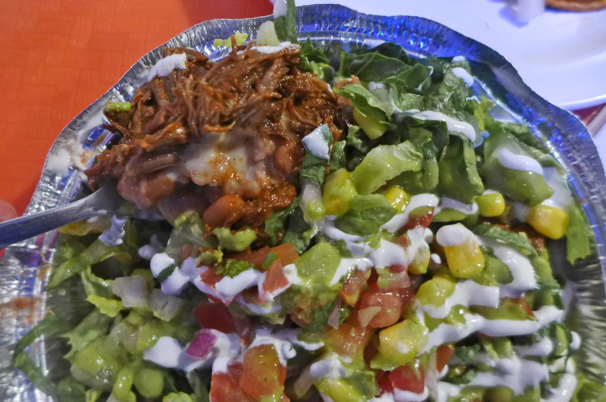 An aluminum container with salad and meat and a half dozen other ingredients.