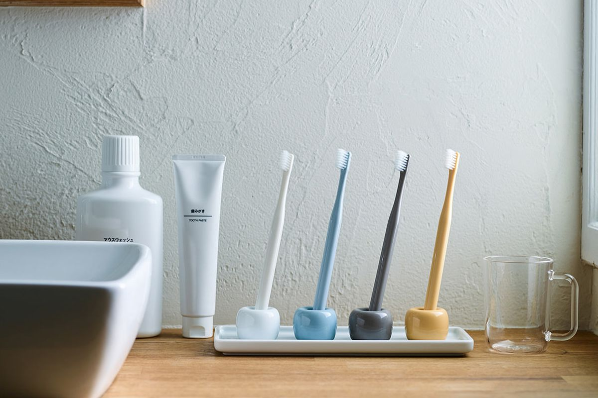 Four small porcelain toothbrush stands holding toothbrushes on a white bathroom counter.