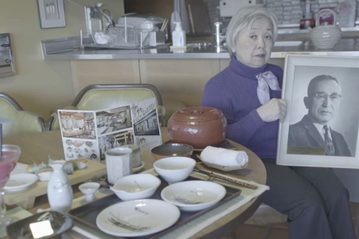 An older Japanese woman holds a framed black and white photo of a Japanese man wearing a suit. She sits next to a table set with plates, bowls and chopsticks.