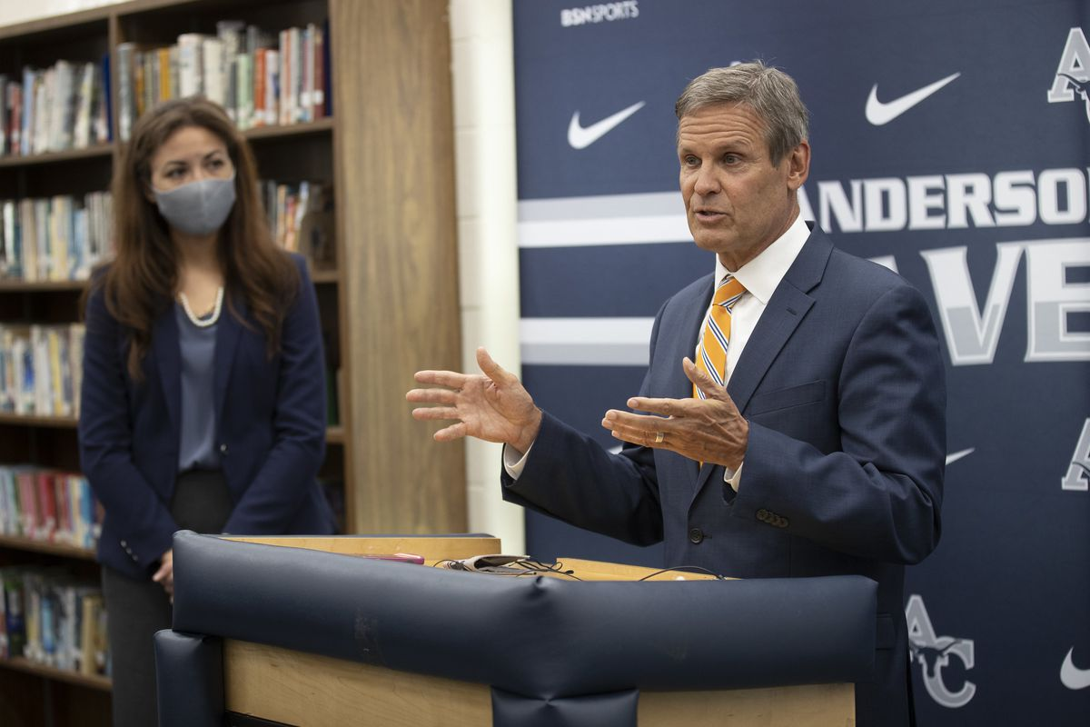 Gov. Bill Lee speaks at a podium while Tennessee Education Commissioner Penny Schwinn looks on