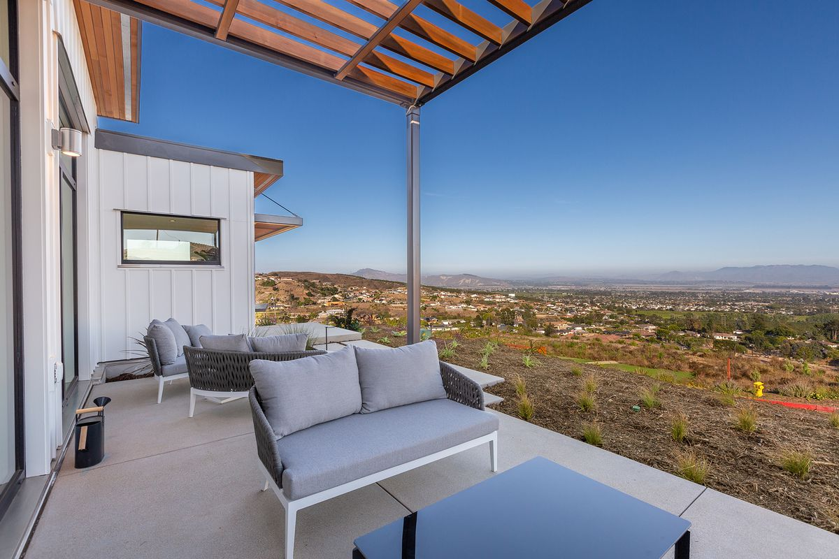Outdoor patio with white and gray seating, overlooking hills.