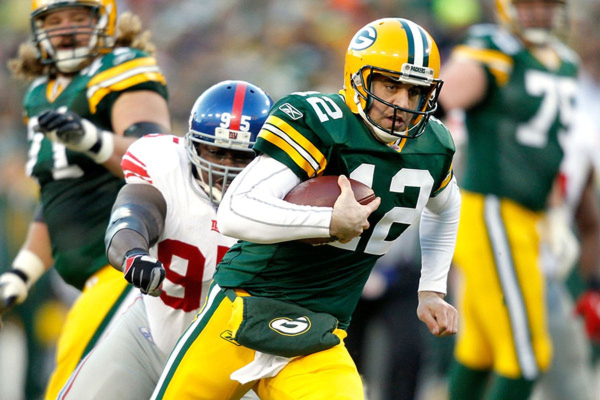 GREEN BAY WI - DECEMBER 26:  Aaron Rodgers #12 of the Green Bay Packers is chased out of the pocket against the New York Giants at Lambeau Field on December 26 2010 in Green Bay Wisconsin.  (Photo by Matthew Stockman/Getty Images)