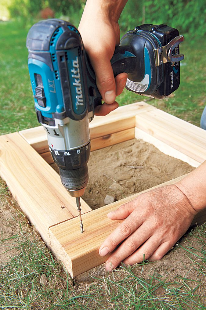 Man Drills In Layers Of Planter Base Boards With Screws