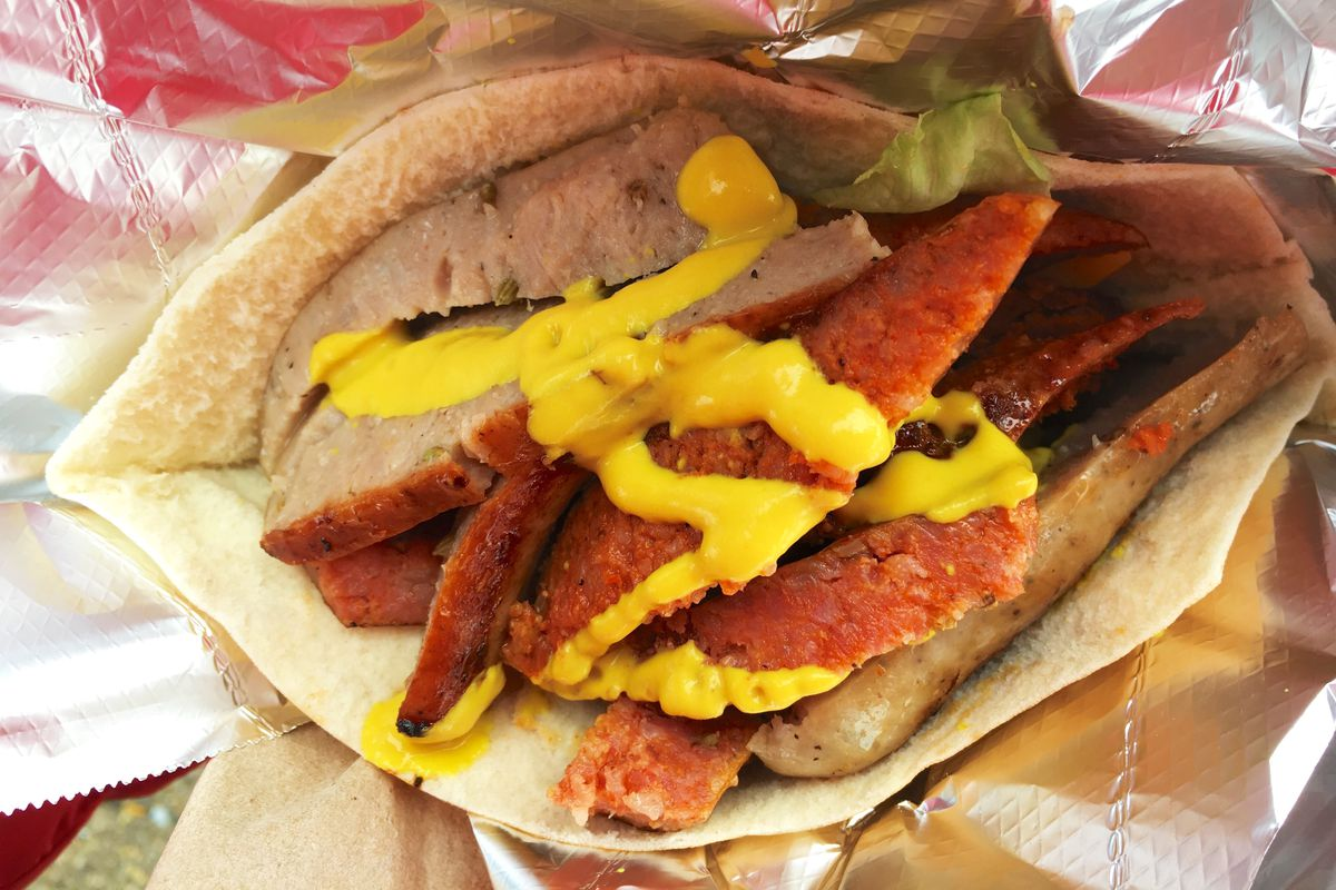 Sliced sausages in a pita pocket drizzled with mustard.