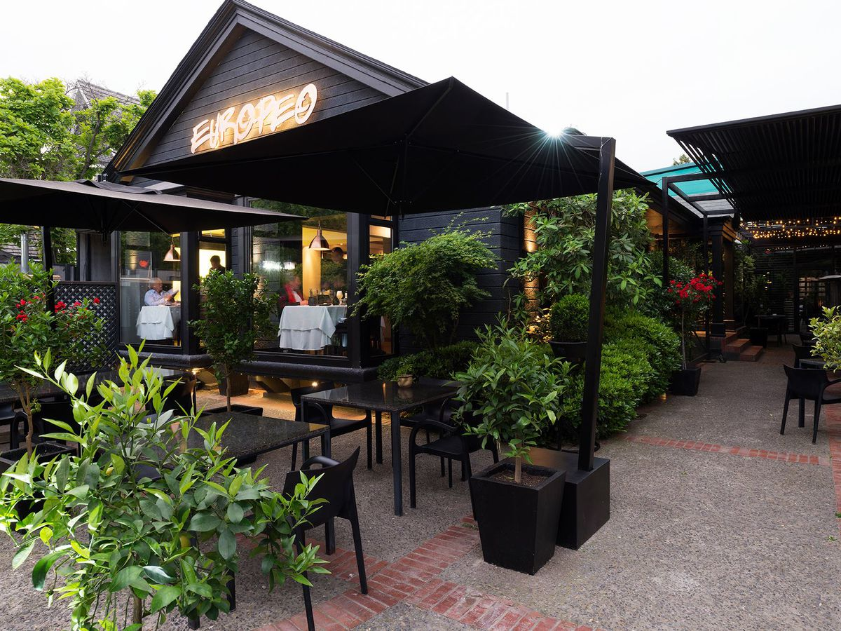 A garden patio and the front awning of a steeped restaurant building with neon name reading Europeo