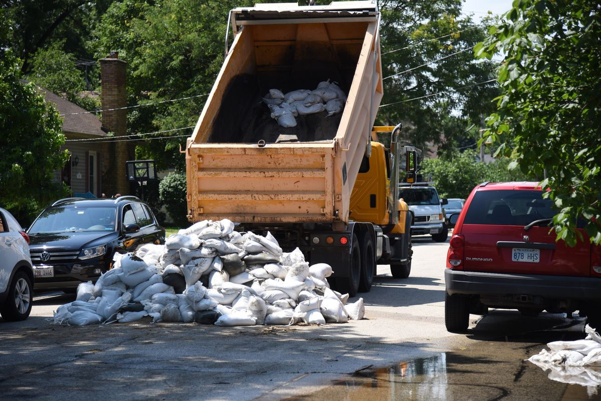 A dump truck drops off another load of sandbags on La Fox River Drive in Algonquin Thursday.   Rick West/Daily Herald