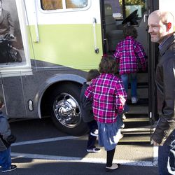 Rob Brown, right, opens the door of a mobile home for his children prior to taking off on a cross-country tour on Nov. 2. The Browns plan to chronicle their journey on Ancestry.com.