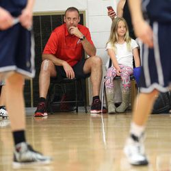 Larry Krystkowiak, head coach for the Utah Runnin' Utes basketball team, watches his sons play in a Team Camp basketball tournament with his daughter Finley at the University of Utah in Salt Lake City on Friday, June 12, 2015.
