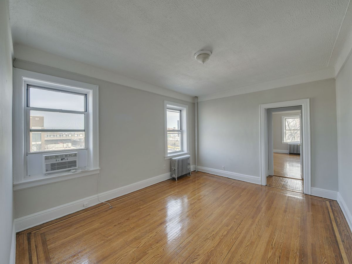 A living area with two windows, hardwood floors, base and crown moldings, and beige walls.