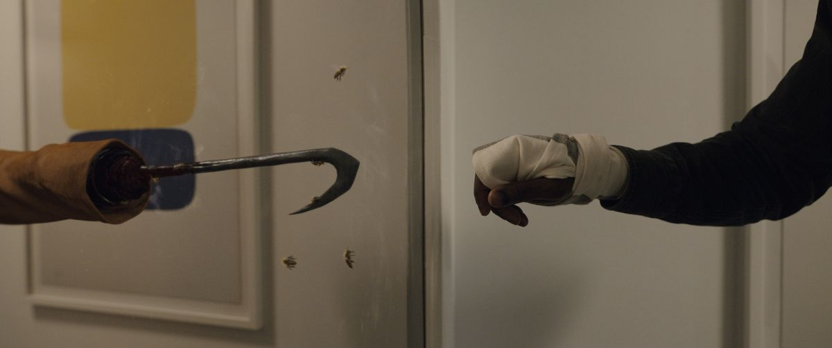 a man with a bandaged hand reaches toward a reflection of Candyman's hook hand in Candyman (2021)