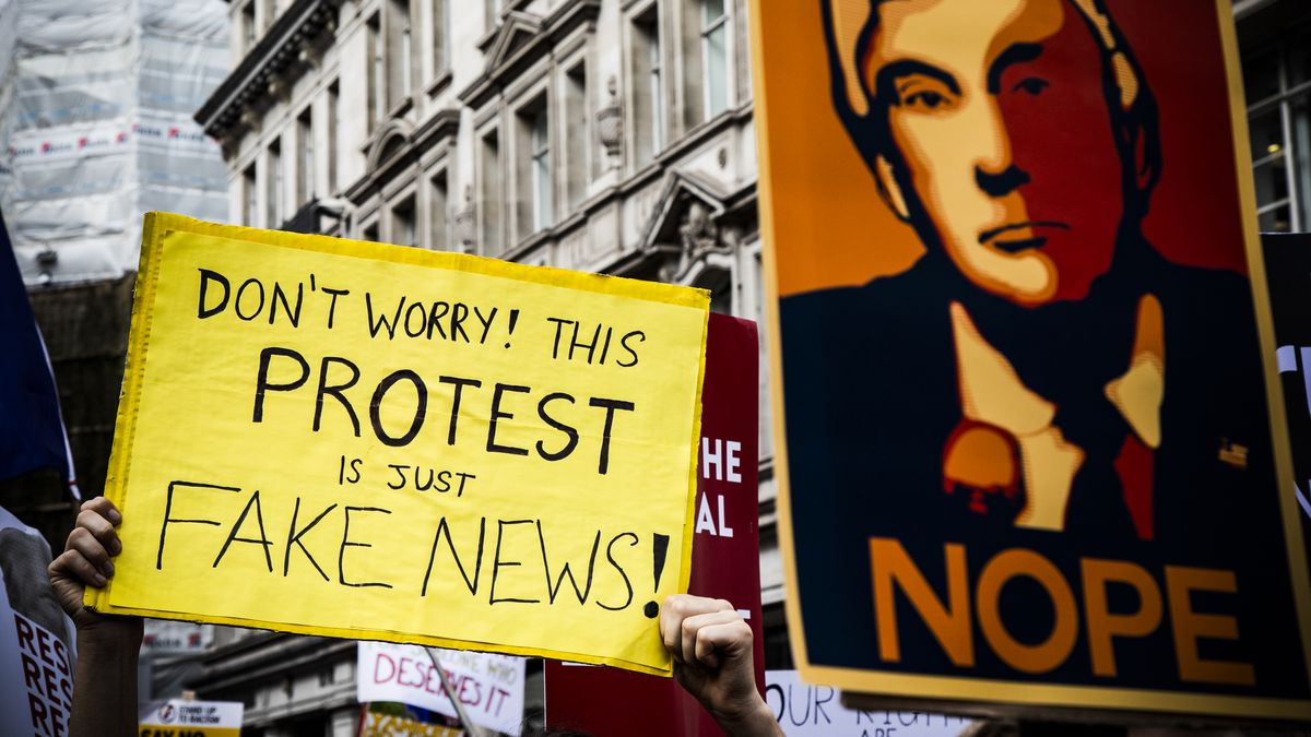 """Protesters carry signs reading """"Don't worry! This protest is just fake news!"""" and """"Nope"""" over a cartoon image of President Donald Trump."""