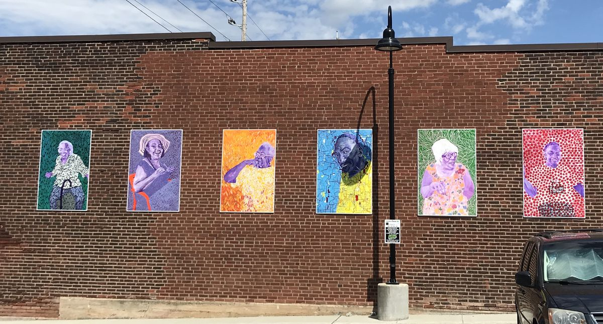 A colorful series of abstract portraits against a plain brick wall.