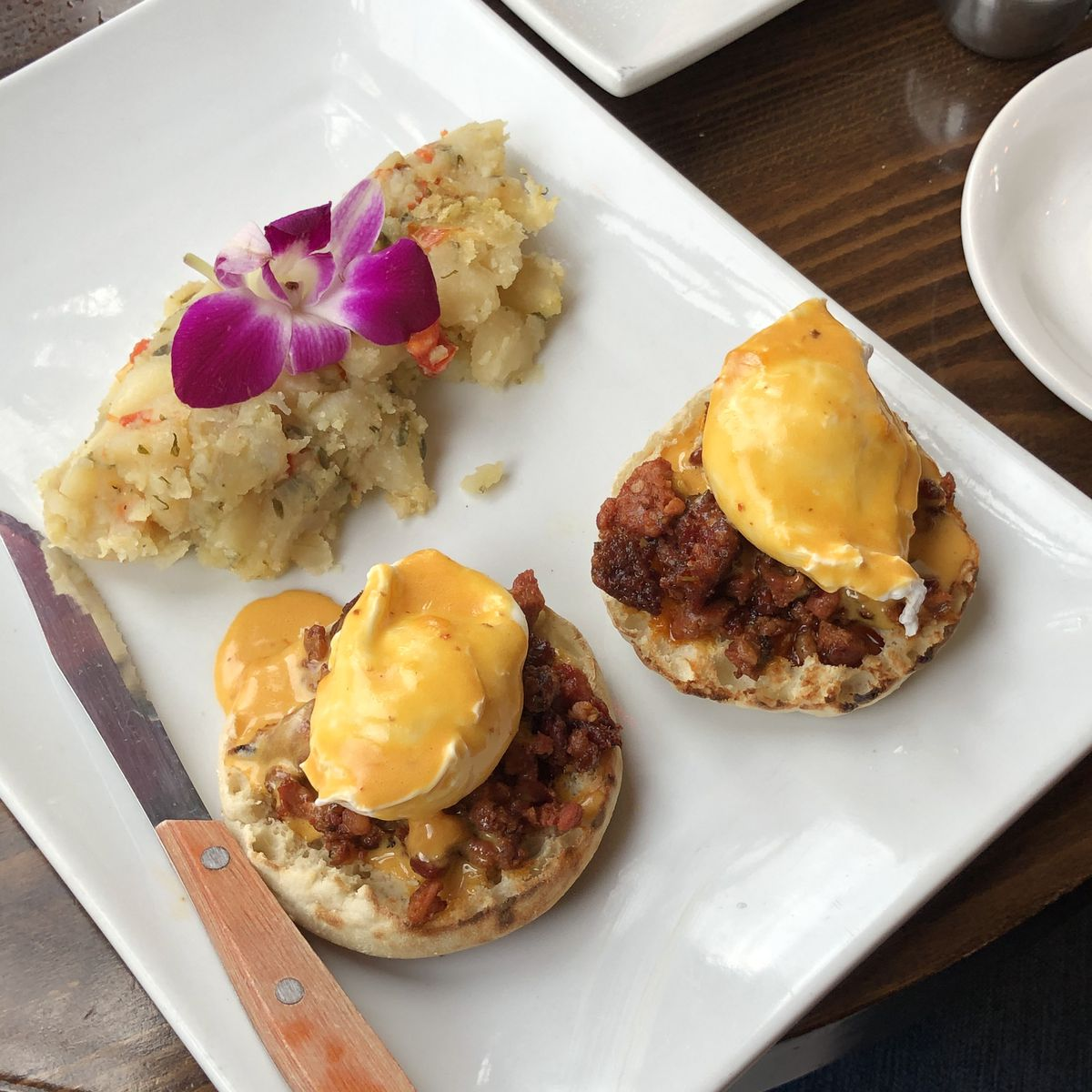 A white plate with a mound of mashed potatoes with a purple flower on top. Two poached eggs with pieces of chorizo sausage and an orange sauce on top of it.