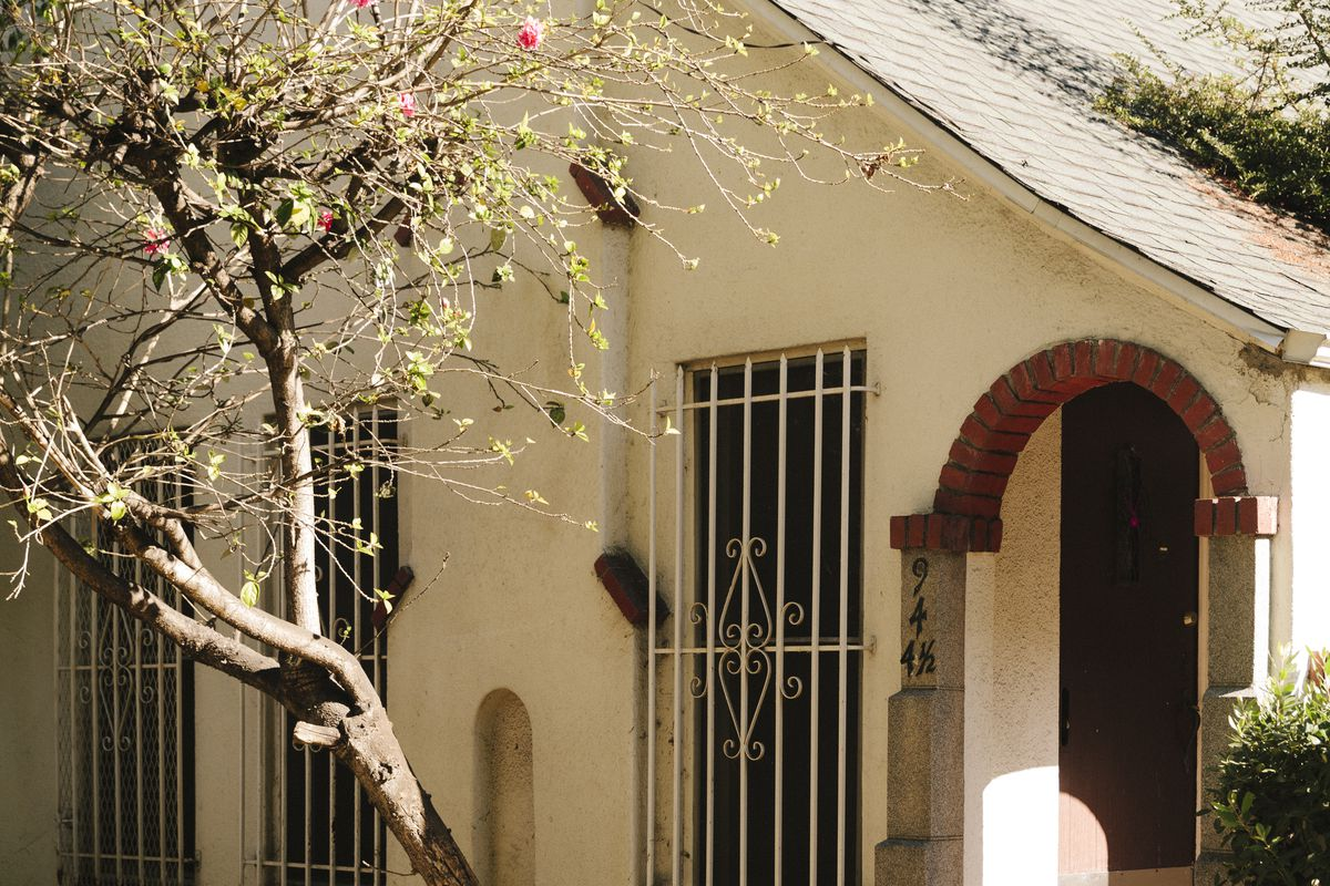 A close up of a beige stucco house with a pitched roof, arched entryway lined in bricks, and a trio of windows covered in iron grills. A tree blooms in front.