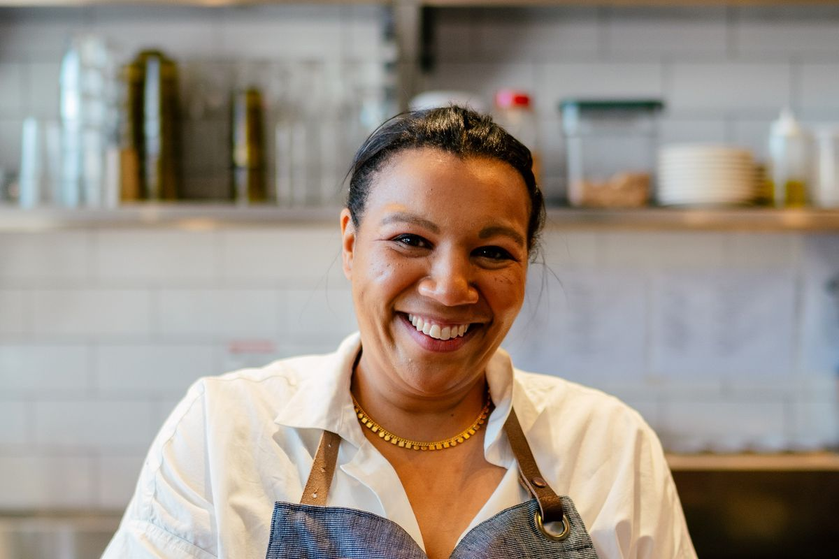 A woman wearing an apron, smiles, appearing to be cooking and holding a container in her left hand